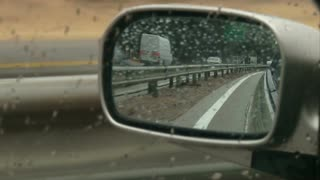 detail-of-left-mirror-car-while-driving-on-a-rainy-day-highway_e126zjuh__S0011